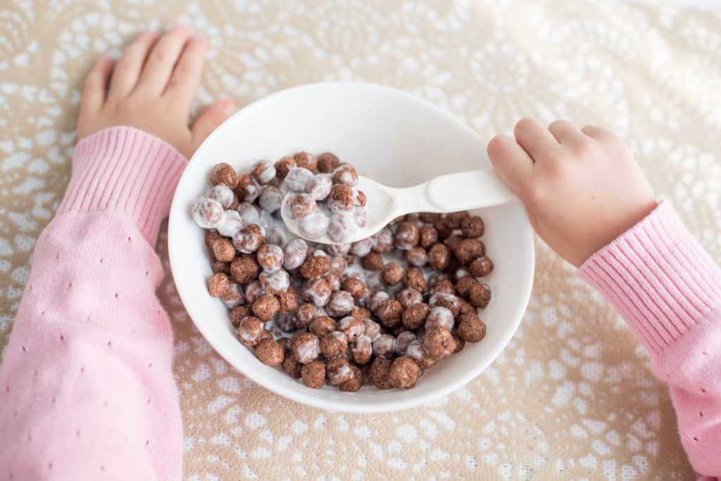 Child eating chocolate cereal from white bowl