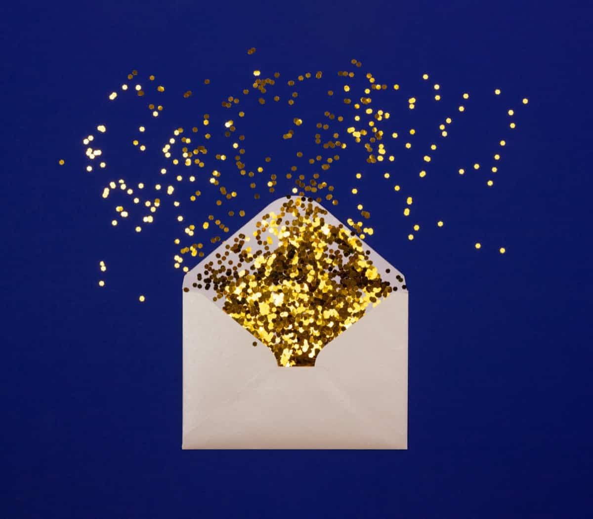 Envelope full of gold glitter against blue background