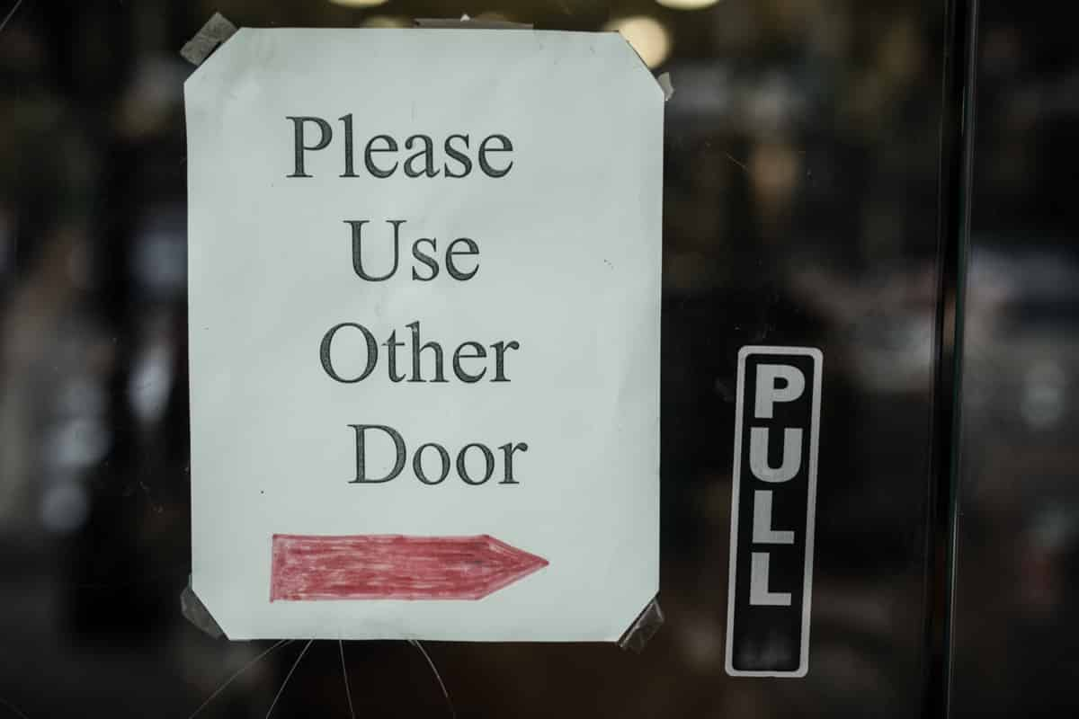 """Please Use Other Door"" sign on glass door"