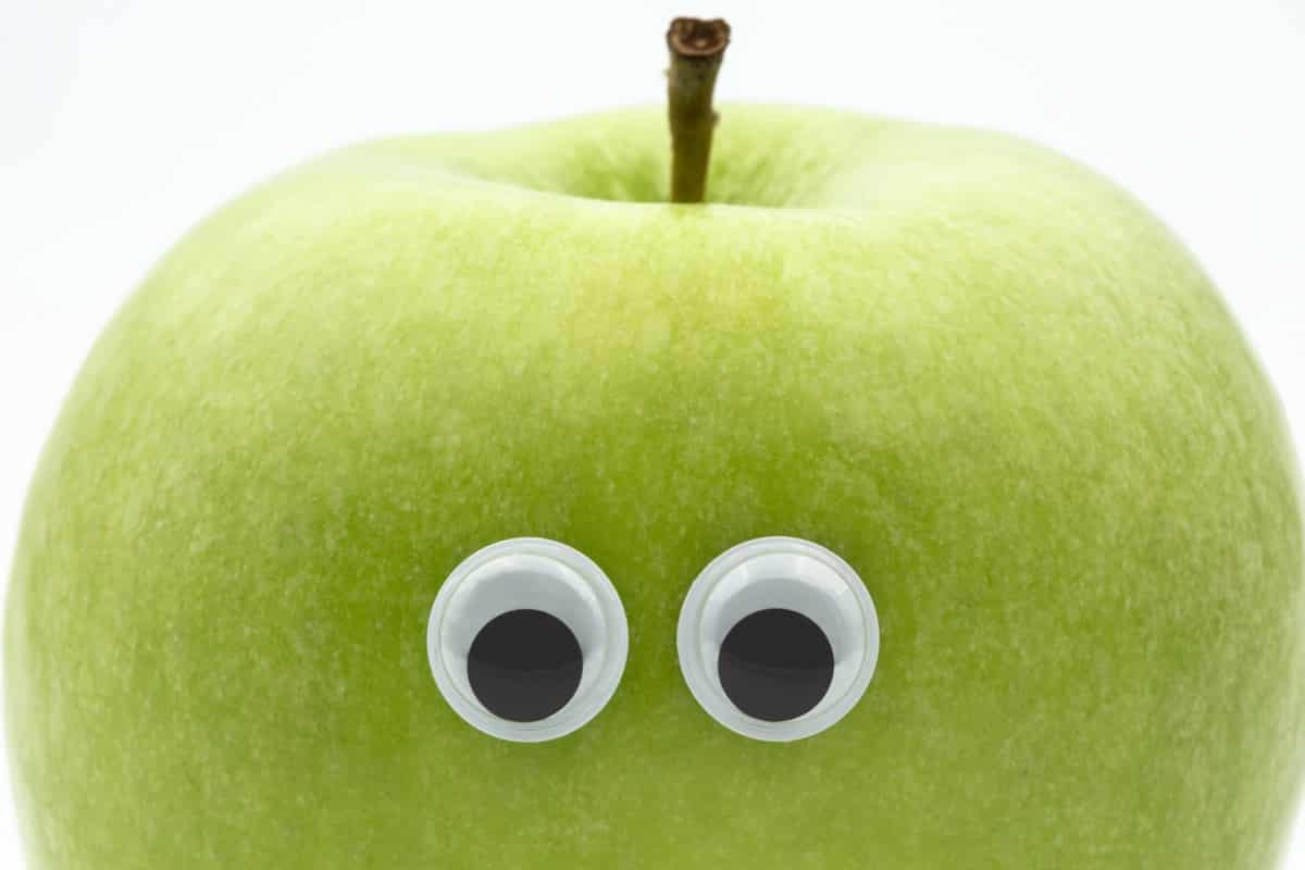 Googly eyes on green apple