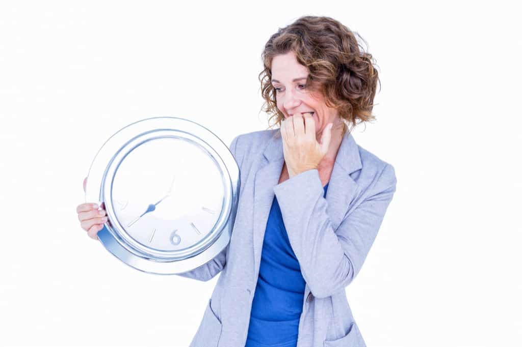 Woman holding clock and looking nervous