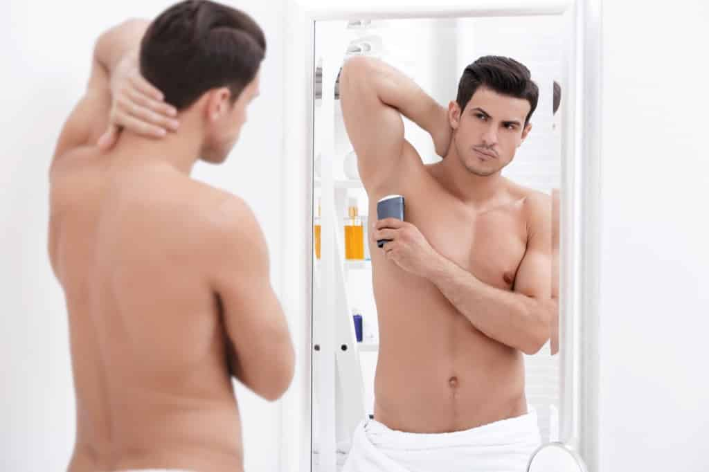 Man putting on deodorant in mirror